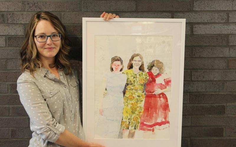 Artist Jacqueline Swanek holds one of her framed watercolour paintings